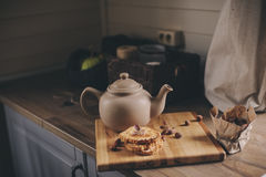 Tea pot and cookies in rustic grey kitchen interior. Slow living in country house concept Stock Images