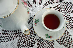 Tea Pot and a Cup of Tea. This a tea pot and a cup of tea sitting on a crocheted lace tablecloth Royalty Free Stock Photo