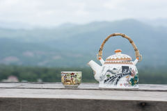 Tea pot and cup on wood table and mountain view. Stock Images