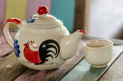 Tea pot and cup on wooden table. Traditional chicken painted on ceramic product. (Not be Trade mark Stock Photography