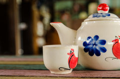 Tea pot and cup on wooden table. Traditional chicken painted on ceramic product. (Not be Trade mark Stock Photo
