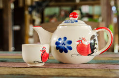 Tea pot and cup on wooden table. Traditional chicken painted on ceramic product. (Not be Trade mark Stock Photos