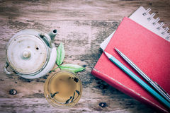 Tea pot, cups and book on wooden table Stock Image
