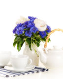 Tea pot and cups on table with blue and white bouquet on white b Royalty Free Stock Photo
