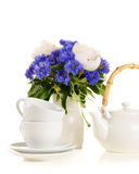 Tea pot and cups on table with blue and white bouquet on white b Stock Photos