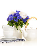Tea pot and cups on table with blue and white bouquet on white b Royalty Free Stock Image