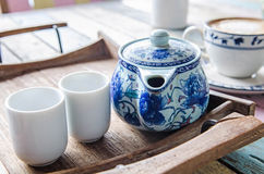 Tea pot and cups on wooden tray. In coffee shop Stock Photo