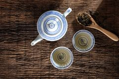 Tea pot and dry tea leaf. Top view of teapot and dry tea leaf on wooden table top royalty free stock images
