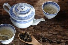 Tea pot and dry tea leaf. Tea pot and dry tea leaf on wooden table toop stock images