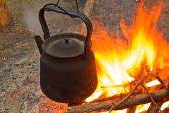 Tea-pot on a fire Stock Photography