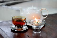 Tea. A tea pot, a tea glass and a candle Stock Photos