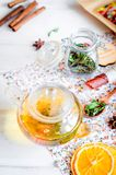 Tea pot with ho greent tea, cup of tea with mint. Lemon slice, dry fruits roll and tea mint leaves with strawberry in a wooden spoon on wooden background, copy stock photography