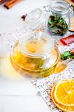 Tea pot with ho greent tea, cup of tea with mint. Lemon slice, dry fruits roll and tea mint leaves with strawberry in a wooden spoon on wooden background, copy stock photos