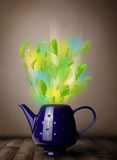Tea pot with leaves and colorful abstract lights. Close up Stock Photo