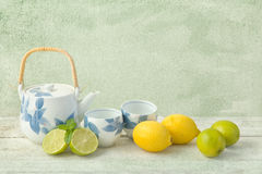 Tea pot and lemons on grunge table Royalty Free Stock Images