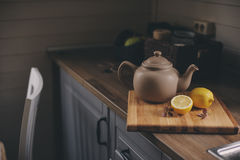 Tea pot and lemons in rustic grey kitchen interior. Slow living in country house concept Stock Images