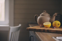 Tea pot and lemons in rustic grey kitchen interior. Slow living in country house concept Royalty Free Stock Photos