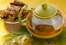 A tea pot, a piece of an apple homemade pie on a plate and autumn leaves Royalty Free Stock Photography