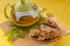 A tea pot, a piece of an apple homemade pie on a plate and autumn leaves Stock Photo