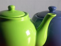 Tea-pot and sugar-bowl. Green tea-pot and blue sugar-bowl on gray background Stock Images