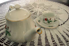 Tea Pot and a Tea Cup. This is a tea pot and a tea cup sitting on a crocheted lace tablecloth Stock Photography