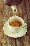 Tea pour cup pot wooden table cafe Stock Photo