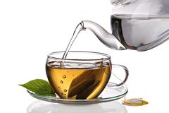 Tea poured into cup. Water being poured into glass tea cup with teabag, isolated on a white background Royalty Free Stock Image