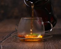 Tea is poured into a cup of lemon and mint. Rustic table Royalty Free Stock Image
