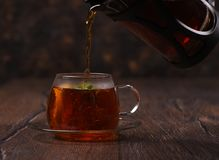 Hot tea is poured into a cup on a wooden table. Tea is poured into a cup with mint rustic table Stock Images