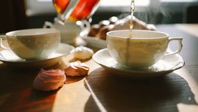 Tea is poured into cups. Beautiful atmospheric steam. Sunday morning. Croissants and desserts. Video footage. Tea is poured into cups. Beautiful atmospheric stock video