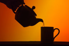 Tea poured from Pot into Cup. Silhouette of teapot pouring a cup of tea into a mug against a tea coloured background Stock Image