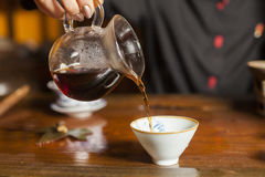 Tea poured from a teapot into a cup. Tea chinese ceremony wooden table Royalty Free Stock Images