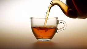 Tea is poured from teapot into glass cup. Slow motion stock video