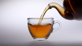 Tea is poured from a teapot into transparent glass cup. Tea is poured from teapot into a transparent glass cup, small teapot with hot freshly brewed tea is stock footage