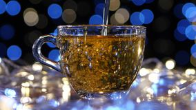 Tea is poured into transparent small glass cup, flickering lights. Tea is poured into transparent small glass cup, in the background small blue and white lights stock footage