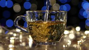 Tea is poured into transparent small glass cup, slow motion. Tea is poured into transparent small glass cup, in the background small blue and white lights burn stock video footage