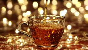 Tea is poured into transparent small glass cup. Slow motion. Tea is poured into transparent small glass cup, in the background small gold lights burn, mag stock footage