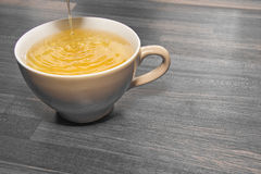 Tea pouring into cup. Yellow tea pouring into cup with wooden background Royalty Free Stock Image