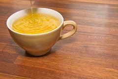 Tea pouring into cup. Last drops of tea pouring into cup with wooden laminate background Royalty Free Stock Photo