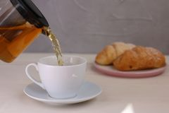 Tea pouring into cup and croissant dessert on light wooden background royalty free stock image