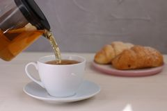 Tea pouring into cup and croissant dessert on light wooden background royalty free stock photo