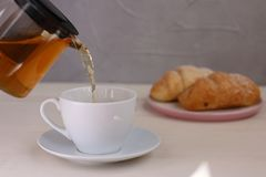 Tea pouring into cup and croissant dessert on light wooden background stock photography