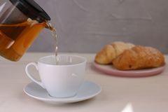 Tea pouring in cup on light background. teapot and breakfast concept royalty free stock images