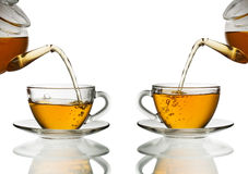 Tea pouring into glass cup Stock Images