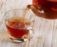 Tea pouring into glass cup Stock Photos