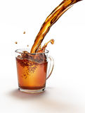 Tea pouring into a glass mug splashing. On a white surface and white background. Clipping path included Royalty Free Stock Photo