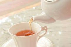 Tea pouring into glass tea cup Stock Photos