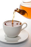 Tea pouring into white cup isolated. On white royalty free stock photo