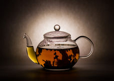 Tea preparation in a glass teapot. On a grey background Royalty Free Stock Photography