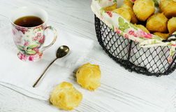 Tea and profiteroles. Tea in color cup and profiteroles in a metal basket Royalty Free Stock Image